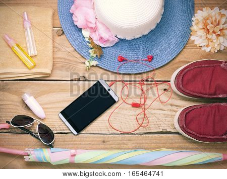 Top view of traveler's outfits Travel stuff Essential outfit and accessory on wood background Summer vacation and travel concept