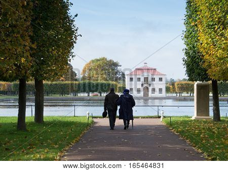 Man and woman strolling with their backs to the camera on tree lined path in Peterhof gardens with pond and Marly Palace in the distance.  Located near St.  Petersburg Russia. Trees have fall foliage.