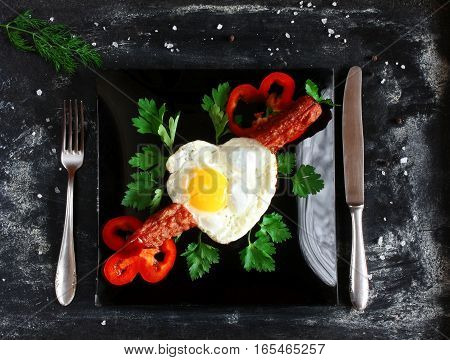 omelet shape heart fried sausage parsley red pepper slices black plate knife and fork dill salt on dark surface