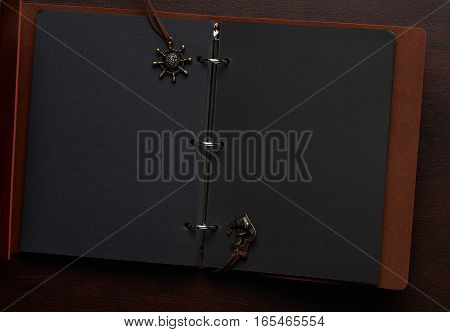 Opened notebook with blank black pages on wooden table view from top