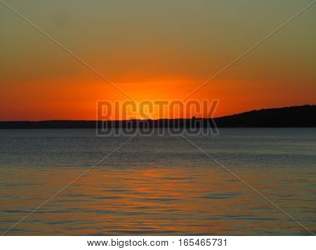 sunset over a blue lake Geneva and an orange sky with silhouette of the far shoreline