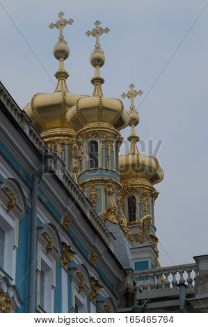 Blue and white exterior of Catherine's Palace with the gold onion domes topped with crosses on the Palace Church. Located near St. Petersburg Russia.