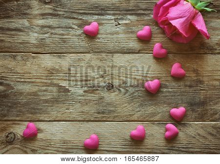 valentine's day one pink rose many heart scattered on an old wooden table