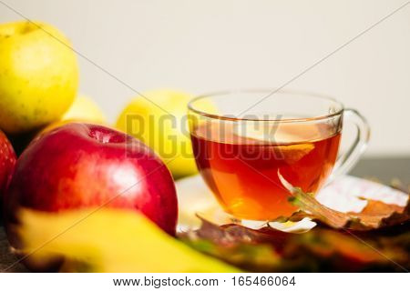 Cup Of Tea With Lemon Next To Ripe Apples