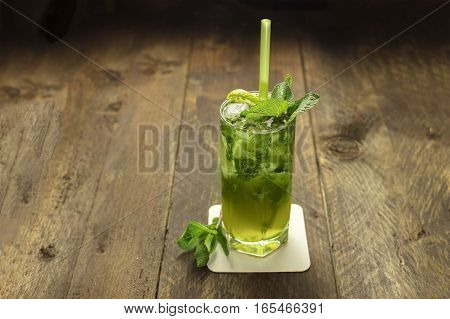 A photo of a mojito cocktail with mint leaves, a wedge of lime, and a drinking straw, on a dark wooden background with copyspace
