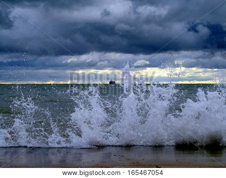 waves smashing against break wall with water intake crib on the horizon