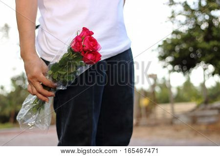 Woman holding bouquet of beautiful red roses on nature bokeh background. Romance and sweet Valentine's day concept