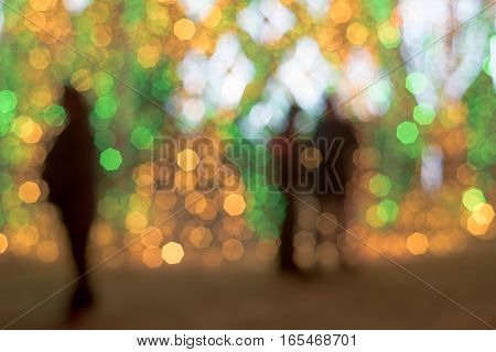 Blurred Christmas holidays city lights with silhouettes of people