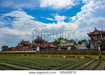Newly planted farmland and Chinese style rooftops of the old Huwei Chifa Matsu Temple in Yunlin County, Taiwan