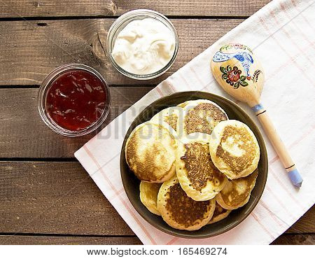 pancakes on a plate with berry jam and sour cream