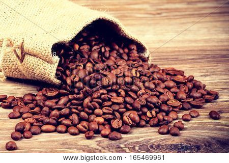 The sack of coffee beans on wooden background. Toned image