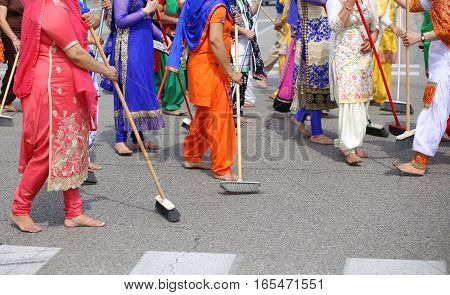 Barefoot Women Of Sikh Religion Sweep The Road During The Celebr