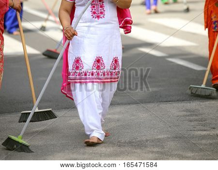 Barefoot Women With Colorful Clothes Sweep The Asphalt Road