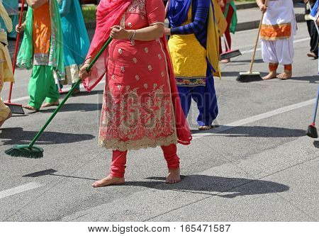 Barefoot Women With Colorful Clothes Sweep The Asphalt Road Duri