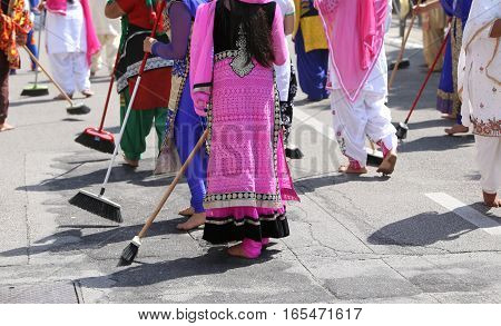 Women With Colorful Clothes Sweep The Asphalt Road During The Ce