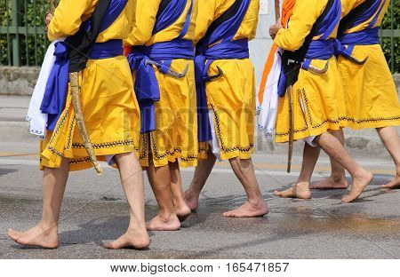 Five Men With Long Dresses Walking Barefoot Through The Streets