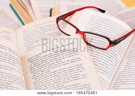 Opened books and eyeglasses close up picture.