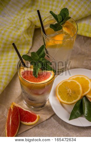 Two Glass Cups Of Water With Red Orange, Lemon, Mint And Ice. Fresh Lemonade