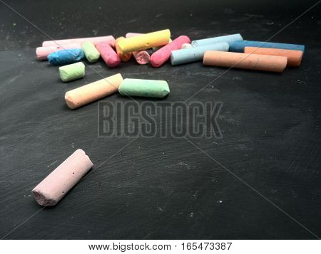 multi colored chalk pieces with text space next to lower chalk piece