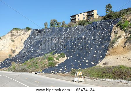 NEWPORT BEACH CALIFORNIA - JANUARY 16 2017: Plastic Covered Hillside. Newport Bluffs hillside covered with plastic to prevent erosion. Seen from Back Bay Drive.