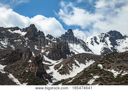 Sharp snowy peaks high in the mountains and clouds