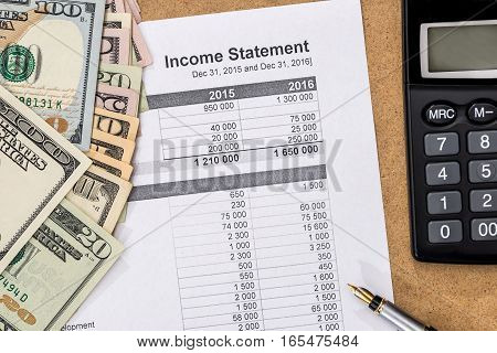 Save money concept - doc income statement with pen calculator and money.
