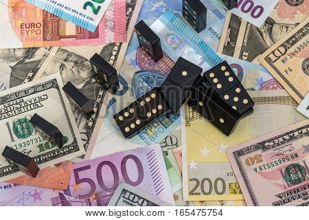 different dominoes on euro and dollar banknotes.