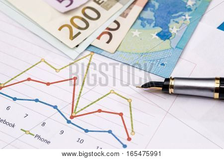 business graphics with euro notes and pen