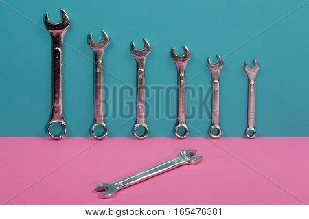 Seven wrenches on a colored background close-up