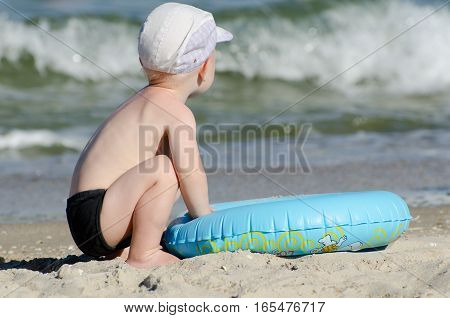 Little blond boy sitting on the seashore with a swimming circle