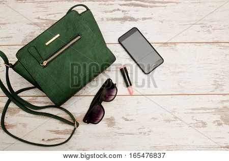 Green ladies handbag sunglasses phone and lipstick on wooden background. Fashionable concept top view