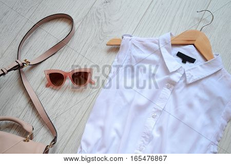 Fashionable concept wardrobe girl. Dress bag and pink sunglasses. View from above