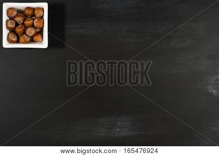 Hazelnuts in a white bowl on the chalkboard. Top view.