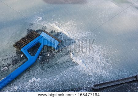 ice scraper cleaning a frozen windshield of a car winter traffic background with copy space selected focus narrow depth of field