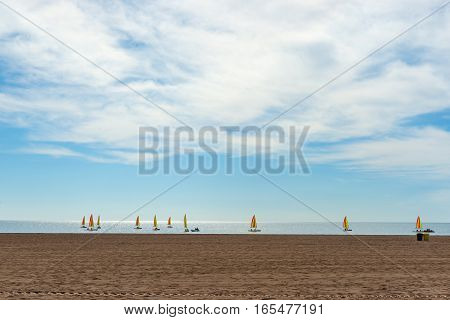 Wide sandy Mediterranean beach with fleet of small yachts with bright sails just off shore in learn to sail lessons Colombiers France.