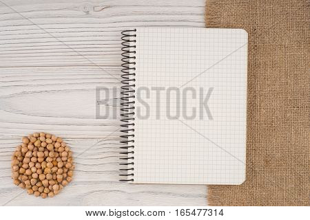 Chickpea and notebook on an old white wooden table. Top view.
