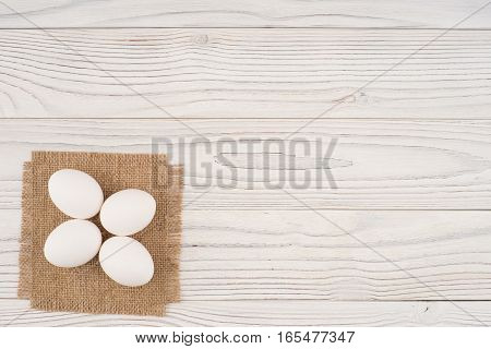 Chicken eggs on white old wooden table. Top view.
