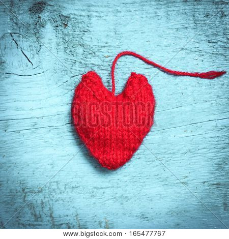 Valentine's Day. Colorful knitted hearts. Red heart on the light blue boards. Valentines day. Heart pendant. Red heart. Valentine cards. Space for text. Toning in bright colors.