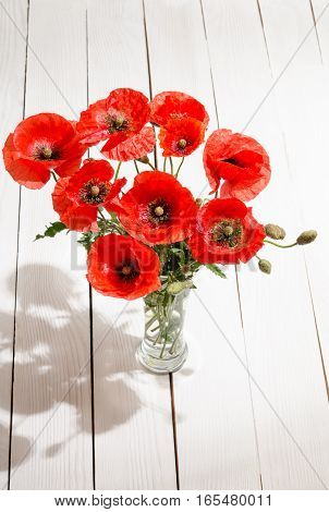 Bouquet Of Red Poppies In Glass Vase On Old White Wooden Table