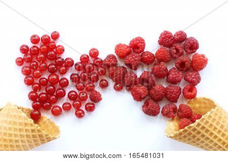 red berries are strewed out of waffle cones in the form of hearts on a light wooden table / impassioned meeting day of lovers