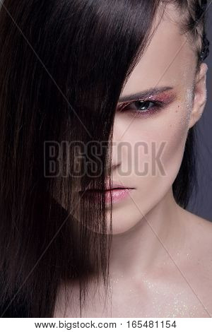 Close-up portrait of beautiful young woman with extraordinary hairstyle and bright make-up