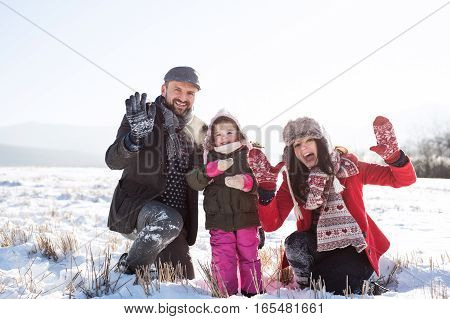 Father and mother having fun with their daughter, playing in the snow, waving. Sunny white winter nature.