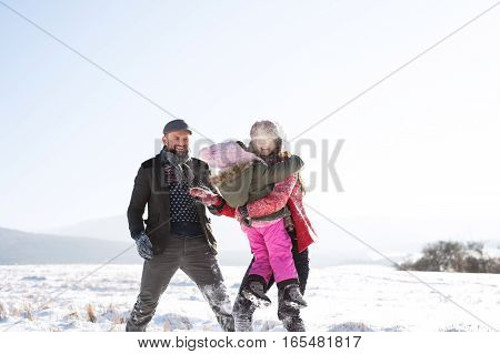 Father and mother outside having fun with their daughter, playing in the snow. Sunny white winter nature.