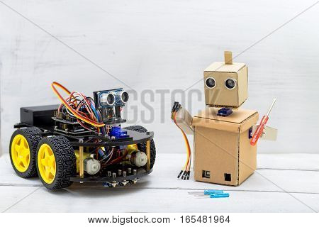 two robots are on the table the robot is repairing another robot