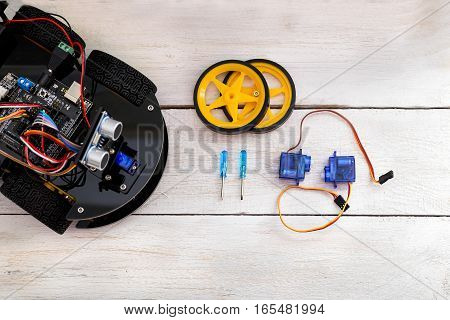 robotics parts. Servo screwdriver lying on a wooden table. view from above