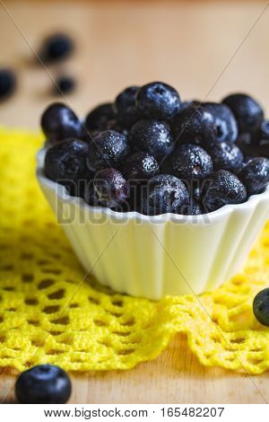 Fresh Blueberries in a white bowl on wooden board