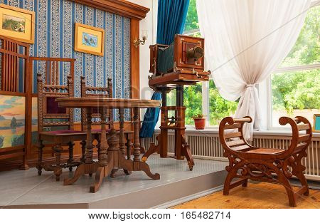 Reconstruction of interior of old photo salon of 19th century with furniture and camera in city of Simbirsk. Russia, Ulyanovsk. July 1, 2014