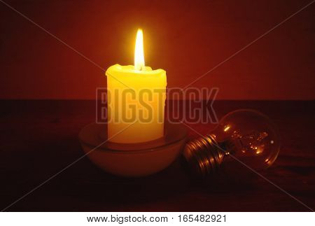 Burning candle and lamp on desktop in darkness. Broken electrical wires via storm.