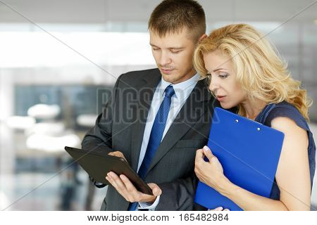 Man And Woman Reading Financial Review At Tablet Pc
