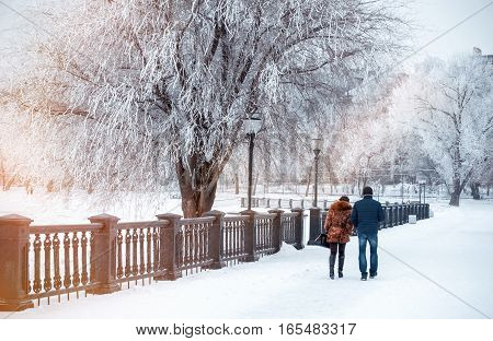 Girl and young man walk along snow-covered quay. Taganrog, Russia, January 7, 2017. Winter landscape of solid sea embankment, trees covered with snow, frosty branches.